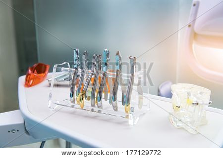 Dental pliers and jaw model. Instruments of stomatologist. Work as a dentist.
