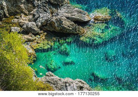 Tourists shorkling between Rocks in Azure Bay of Beautiful Paleokastritsa in Corfu Island, Greece.