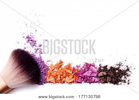 crushed eye shadows and brush isolated on white