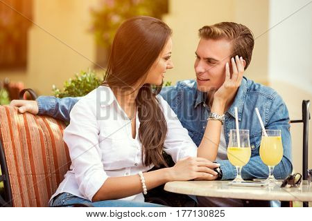 Beautiful young loving couple sitting together in cafe  while woman touching  her boyfriend and smiling,  enjoying every minute together
