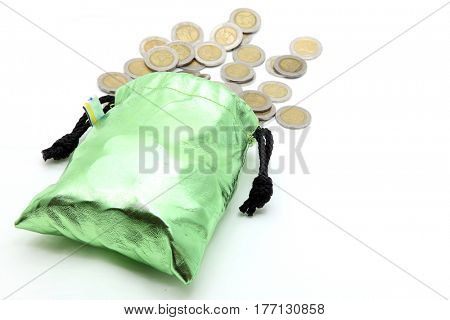 coins spilling out from green money bag or purse isolated on white