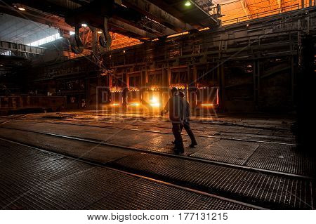 Steelworkers near the working open hearth furnace