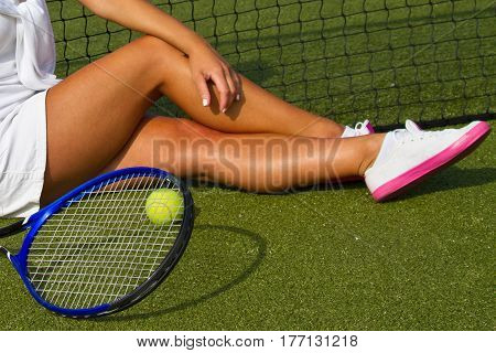 Beautiful girl tennis player sitting on training