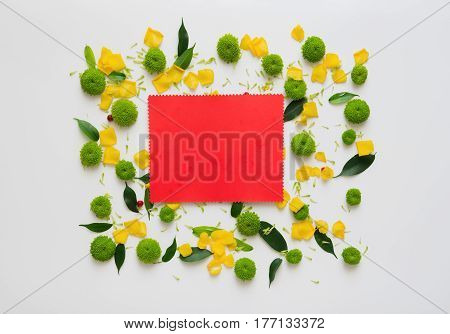 Red paper with wreath frame from rose and chrysanthemum flowers, ficus leaves and ripe rowan on white background. Overhead view. Flat lay.