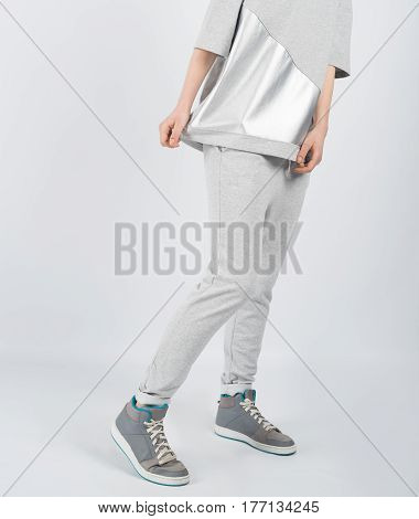 Lower body section of a young beautiful girl wearing grey clothes and sneakers posing isolated on white background.