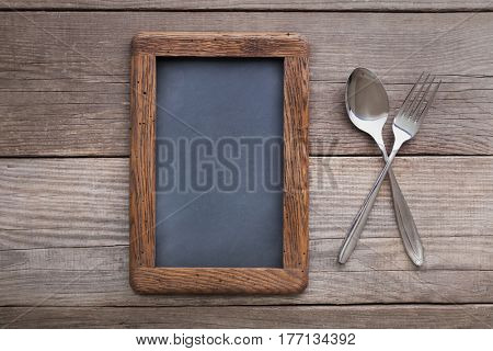 fork and spoon on a rustic table with a rough frame for chalk records, blackboard next to the dining utensils, top view