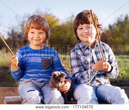 Happy boys go fishing on the river with pet, Two children and kitten of the fisherman with a fishing rod on the shore of the lake