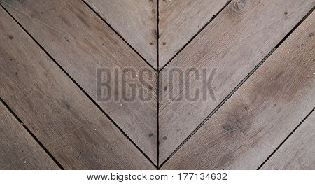 Brown wood slat floor with arrow shape fasten with nail