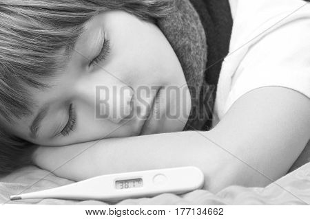 Little sick boy lying on bed with digital thermometer
