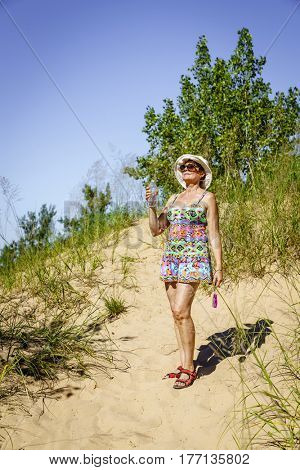 Happy woman with water bottle on a trail through Sleeping Bear Dunes in Northern Michigan