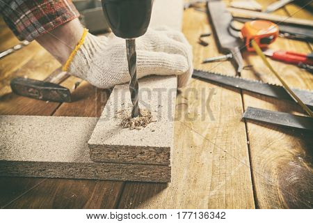 Man drills the wooden plank