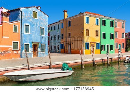 Typical colorful houses along narrow canal on Burano island in Italy.