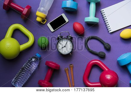 Time for exercising clock and sport equipment with yoga mat background