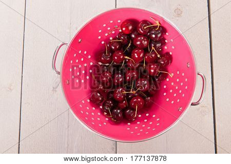 Fresh washed cherries in pink colander on wooden underground