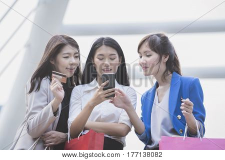 Working women chating about online shopping in the office building