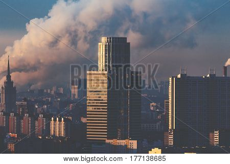 Close-up shooting from top of early morning metropolitan city: office business skyscrapers residential buildings towers huge column of smoke from chimneys in background hazy horizon Moscow