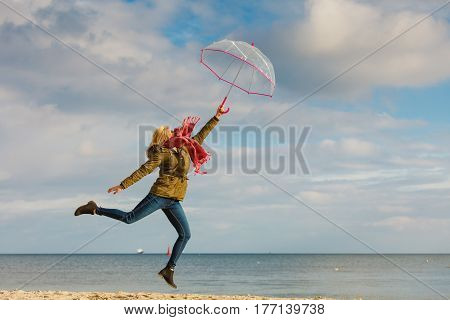 Happiness enjoying cold autumn weather feeling great concept. Woman jumping with transparent umbrella on beach near sea sunny day and clear blue sky