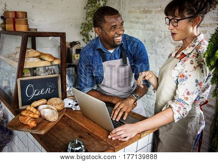 Couple Using Laptop in Bakery Shop