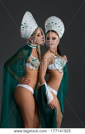 Pretty sexy girls posing in russian kokoshniks, bead masks on faces, white underwear studio portrait black background