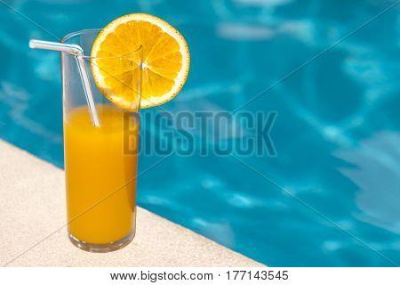 Glass of orange juice with orange slice near the swimming pool