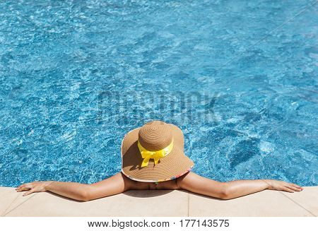 Woman in hat having sunbathing at the swimming pool