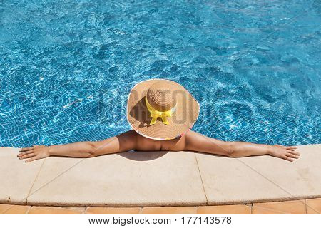Woman in hat relaxing on swimming pool