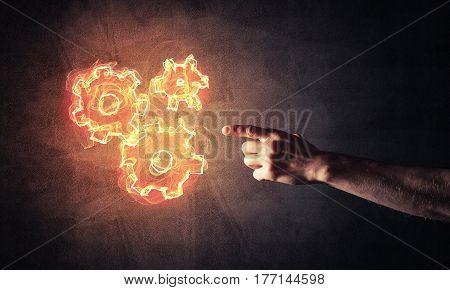 Hand of man presenting fire gear mechanism on dark background