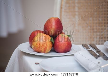 Red apples in a plate on white table