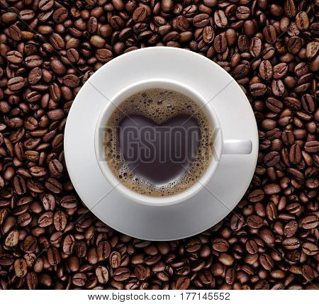 coffee lover sign - black coffee cup on top Pile of raw brown coffee beans with heart shape. love symbol on fresh coffee mug - Top view
