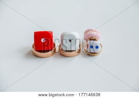 2 wedding ring together on white background and one small kids child girl ring like a symbol of love. Family wedding rings. math and love. mathematical equation. love question. dice