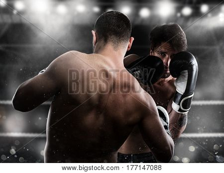 Boxer in a boxe competition beats his opponent with a punch