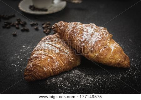 Traditional french breakfast croissant with sugar and coffee on black stone table