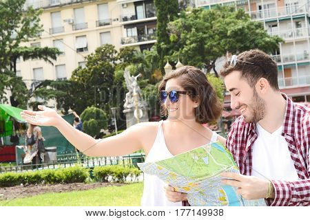 Portrait of a young beautiful couple on a trip and looking at the map. Travel concept. Outdoors.