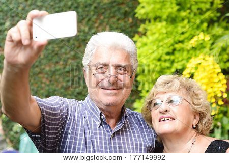 Portrait of an elderly couple taking selfie with smartphone. Outdoors.