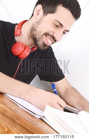 Attractive young man studying with digital tablet and books. Indoors.