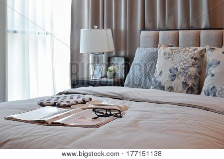 Elegant Bedroom Interior Design With  Floral Pattern Pillows On Bed And Decorative Table Lamp.