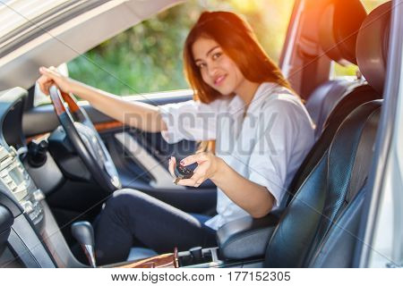 Young asian woman driver driving a car on the road in countryside and hand presses on the remote control car alarm systems