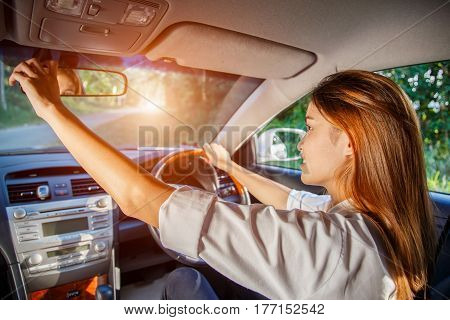 Young asian woman driver adjusting her rearview mirror in the car.
