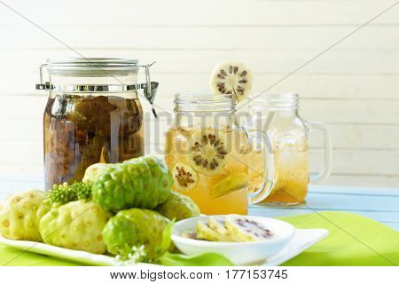 Noni fruit in the dish and noni slice with noni fermented and noni juice on green checkered fabric