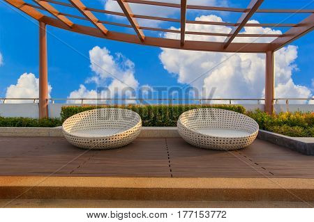 Relax corner on condominium rooftop garden with chairs on blue sky background
