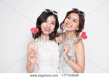 Two Fashionable Women In Nice Dresses Standing Together And Holding Red Heart Shape.