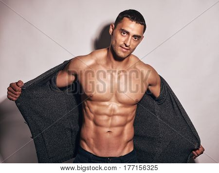 Muscular hot young man taking off his shirt