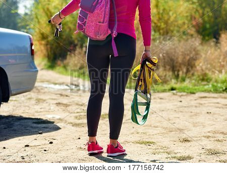 Close up photo of young sportswoman with equipment going to training about car