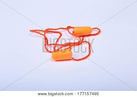 Orange earplug on thread. Earplug to reduce noise on a white background
