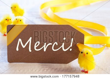 Label With French Text Merci Means Thank You. Easter Decoration Like Chicks. White Wooden Background. Card For Seasons Greetings
