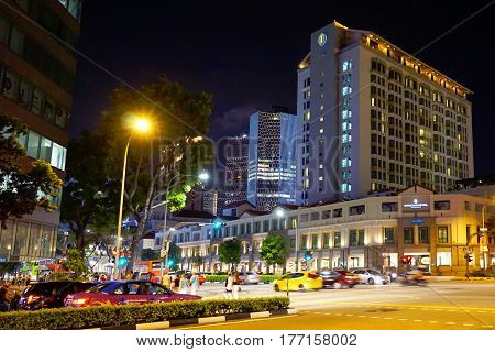 Singapore, Singapore - February 11, 2017: People and cars move alongside the night street in the Bugis Junction in Singapore.