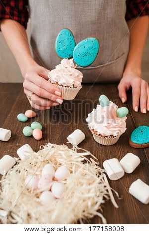 Decorated cup cakes and nest with small white eggs for easter celebration on wooden table. Holiday gift, small business, delivery of sweets, craftmanship concept