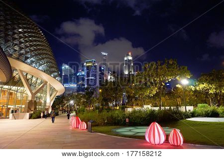 Singapore, Singapore - February 11, 2017: People move alongside the night street in the Waterfront near Opera building in Singapore.