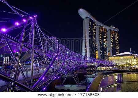 Singapore, Singapore - February 11, 2017: People move across the Singapore river by Helix Bridge near Marina Bay Sands skyscraper.