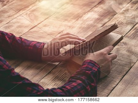 Male hands holding an old book on a wooden table close up